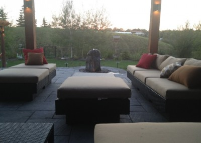 landscape design at sunset with decorative stone and seating area