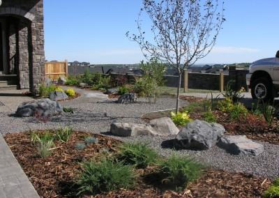 front yard landscape design with plant beds and decorative stones